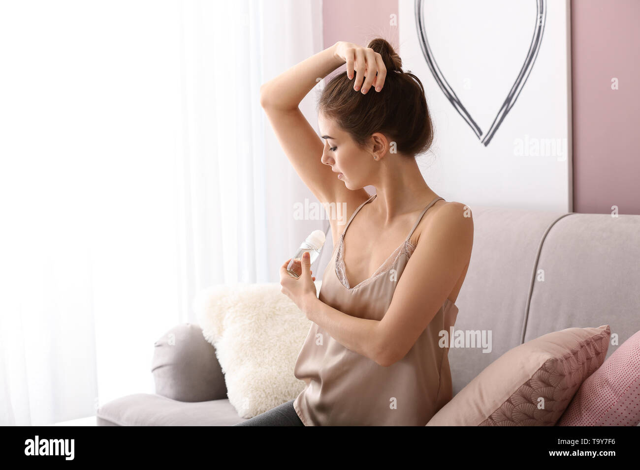 Beautiful young woman with deodorant at home - Stock Image