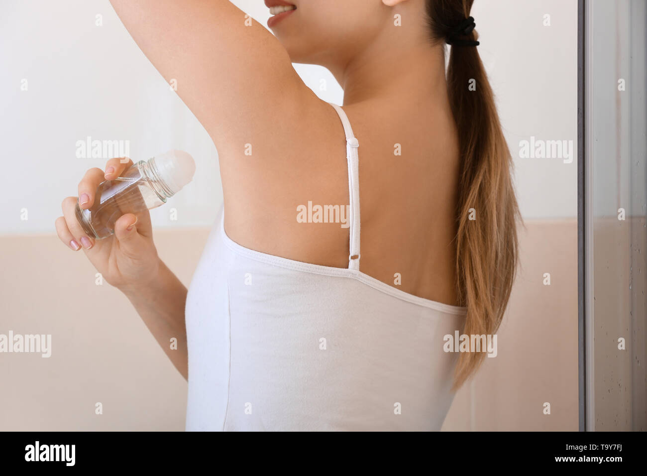 Beautiful young woman with deodorant in bathroom - Stock Image