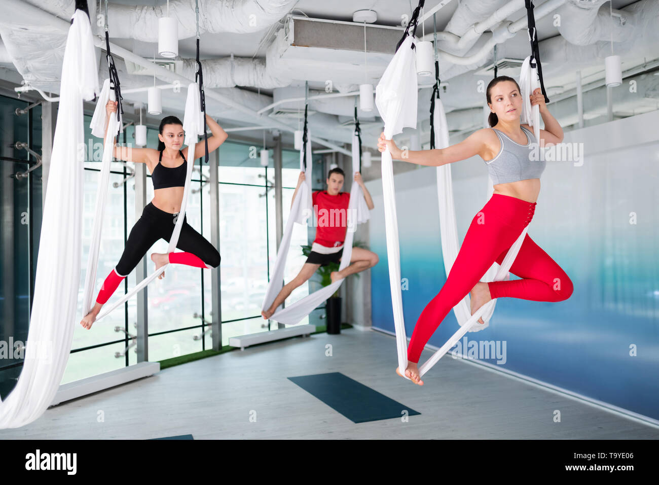 Two women and man wearing comfy sport clothing doing flying yoga - Stock Image