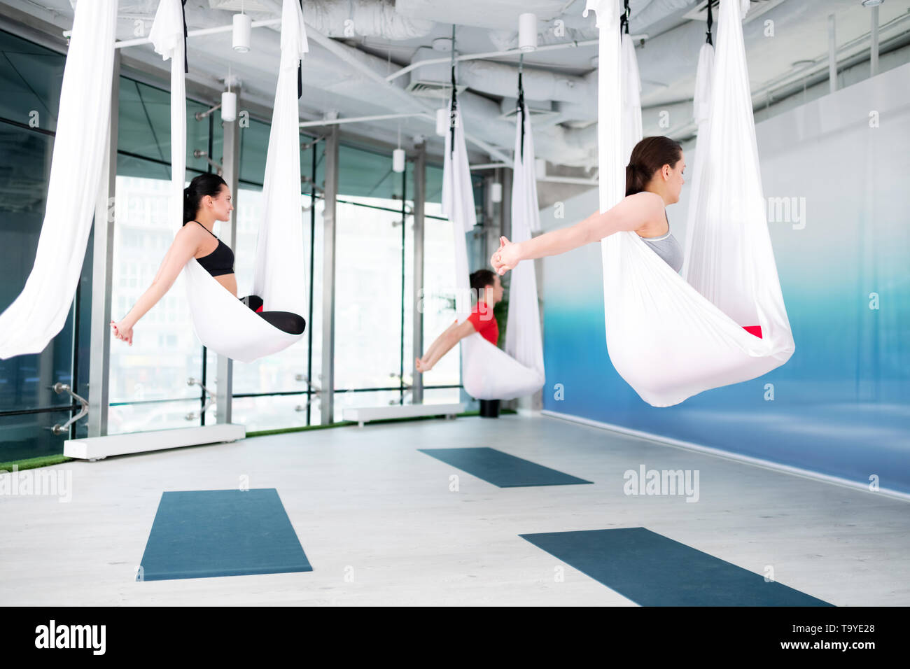 Dark-haired yoga teacher showing nice poses for aerial yoga - Stock Image