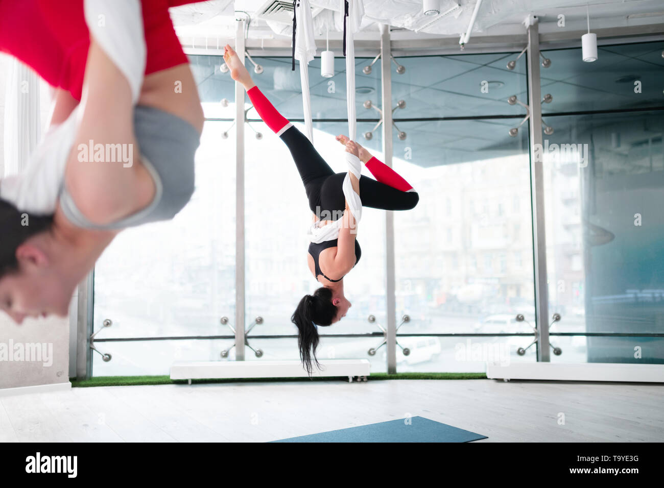 Two women wearing comfy leggings doing aerial yoga together - Stock Image