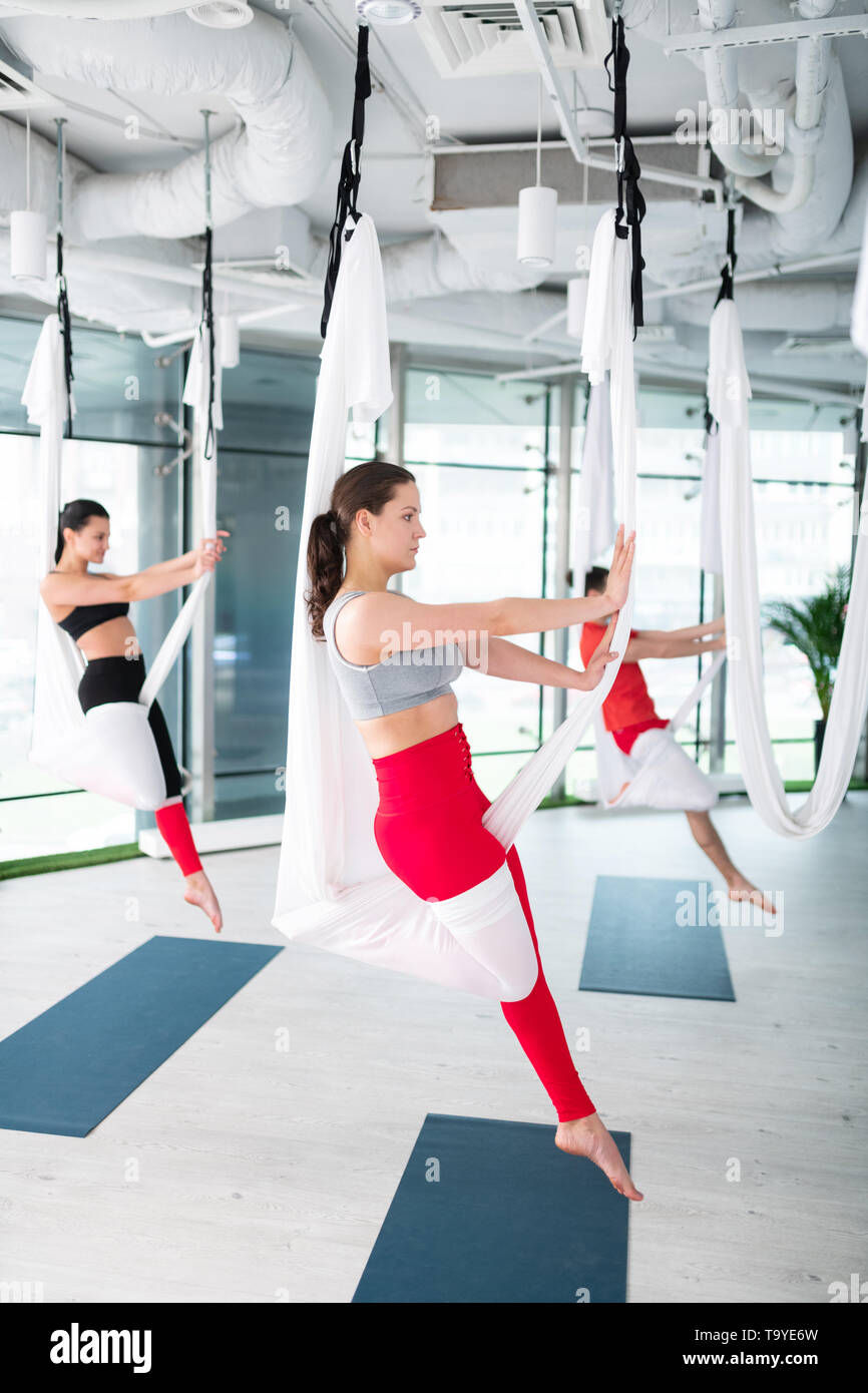 Dark-haired yoga trainer showing nice pose for aerial yoga - Stock Image