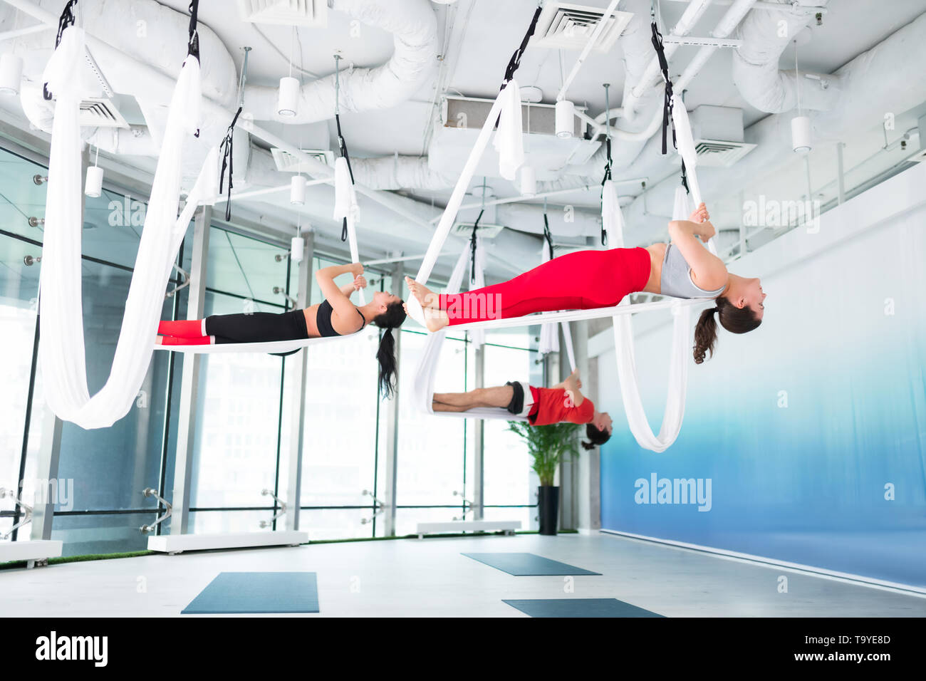 Two women and man wearing comfy clothes doing aerial yoga - Stock Image