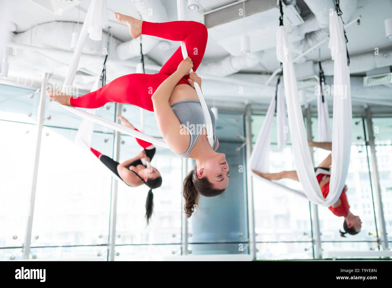 Dark-haired trainer in red leggings showing nice aerial yoga pose - Stock Image