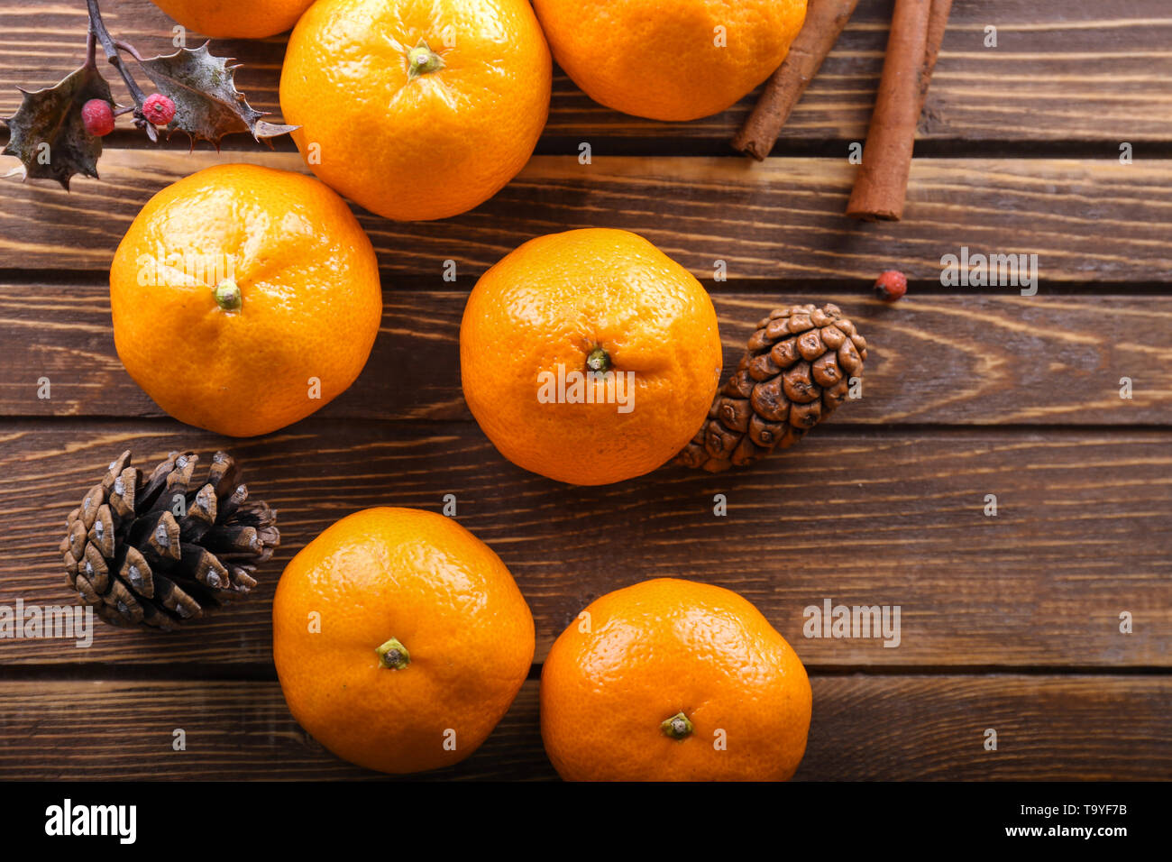 Ripe sweet tangerines and cones on wooden background - Stock Image