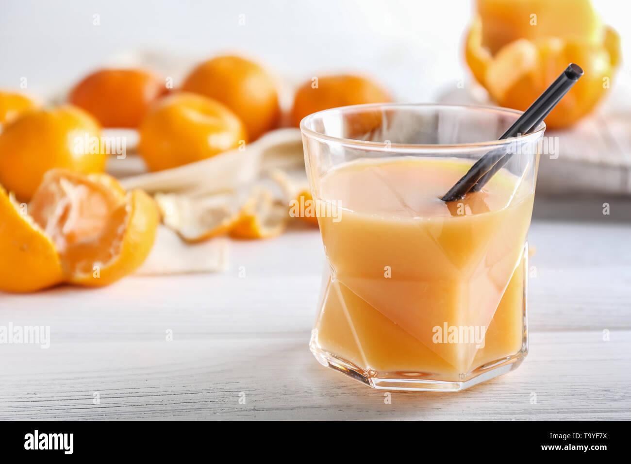 Glass of sweet tangerine juice on table - Stock Image