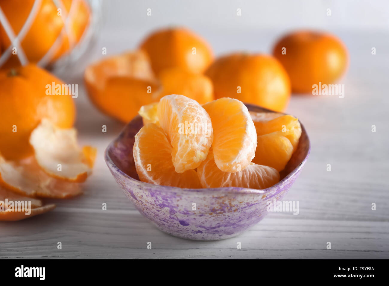Bowl with ripe tangerine cantles on wooden table - Stock Image