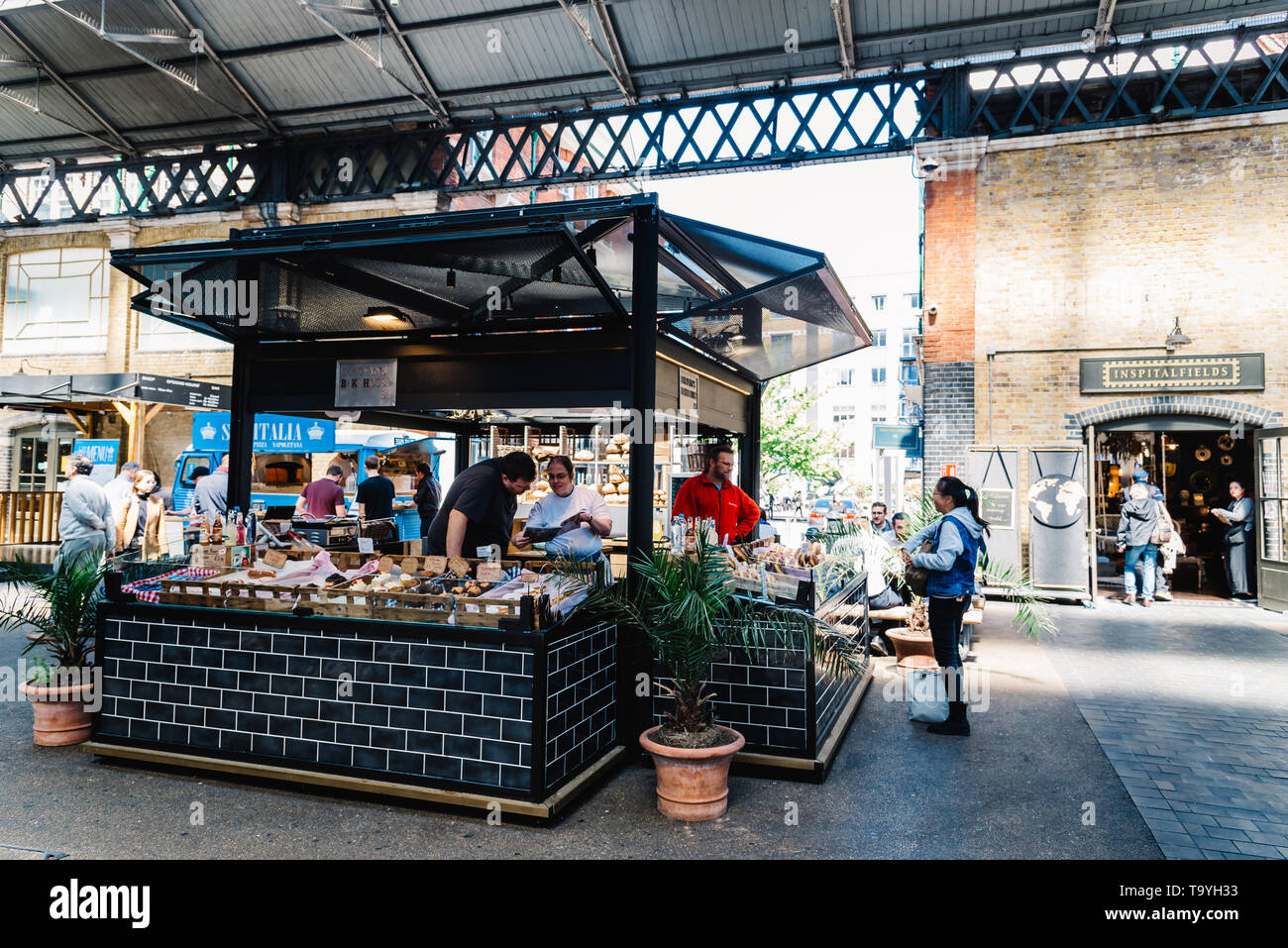 London, UK - May 14, 2019:  Old Spitalfields market with unidentified people. Bakery and pastry stall. The market  hosts arts and craft and street foo Stock Photo