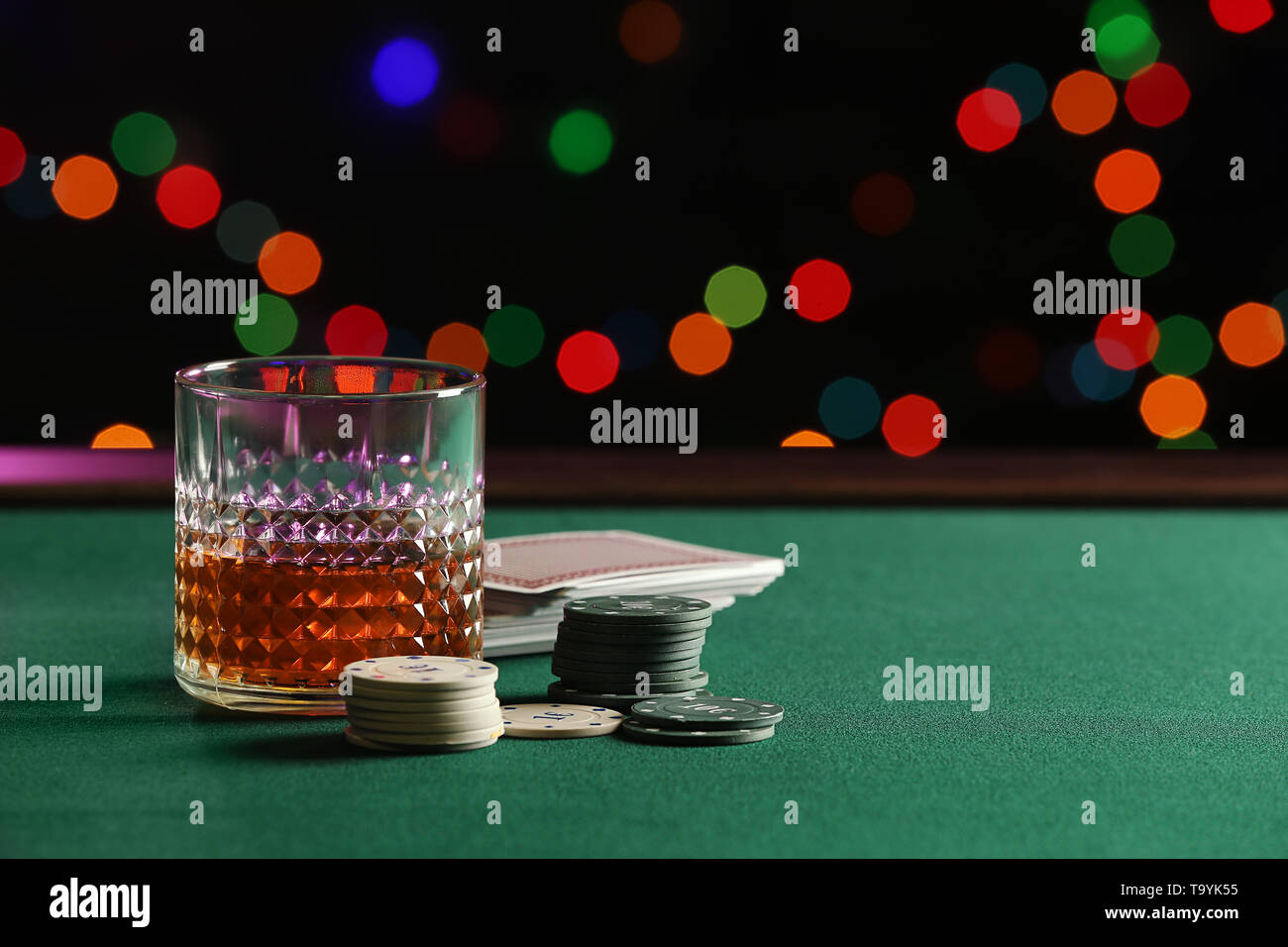 Chips, glass of whiskey and cards on table in casino - Stock Image