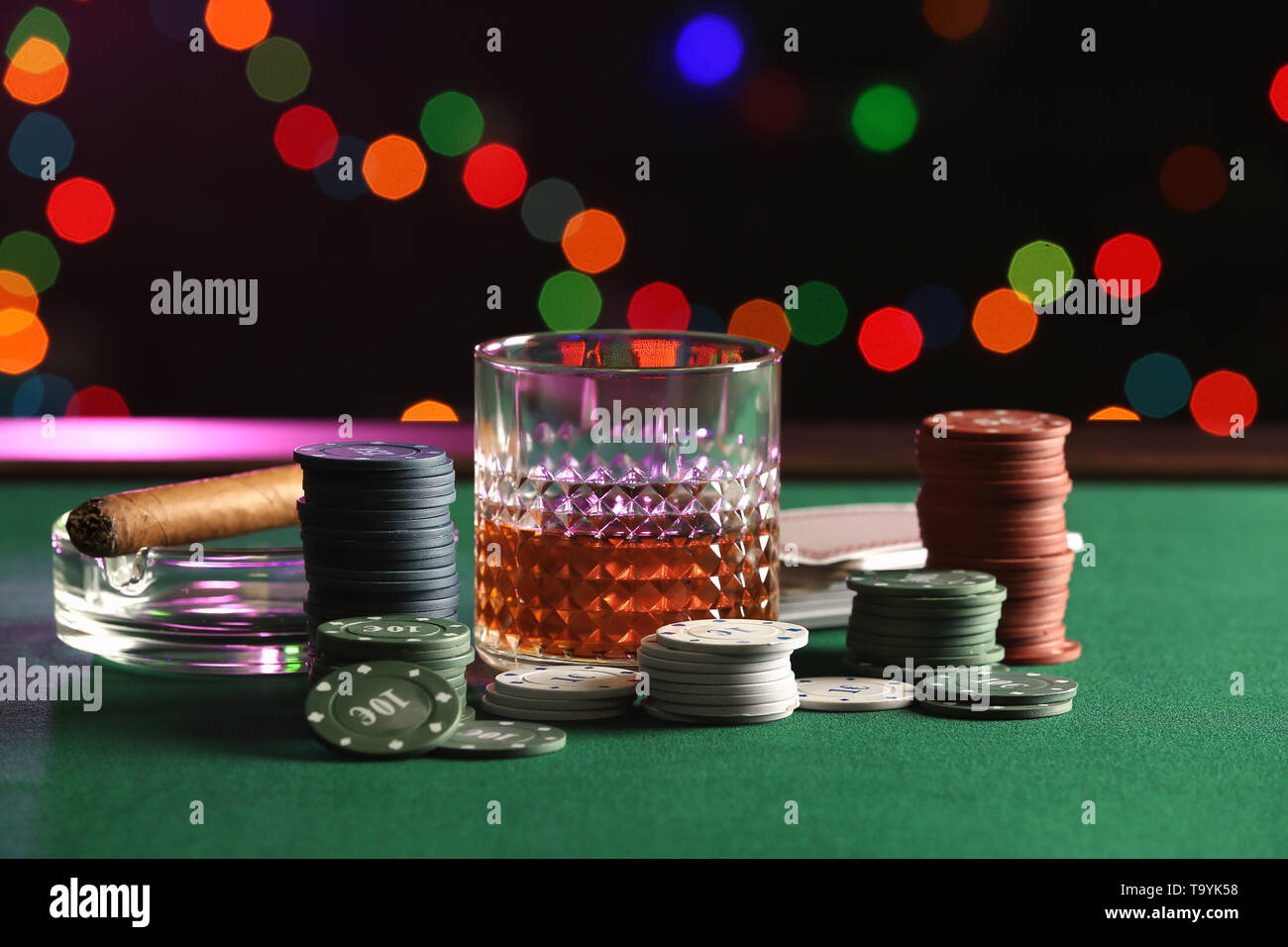 Chips, glass of whiskey and cigar on table in casino - Stock Image