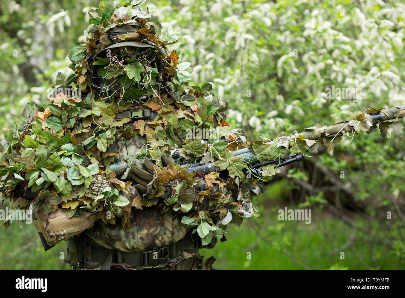 Closeup portrait of a military sniper men in camouflage green army clothes with a gun on his hand on the background of flowering trees - Stock Image