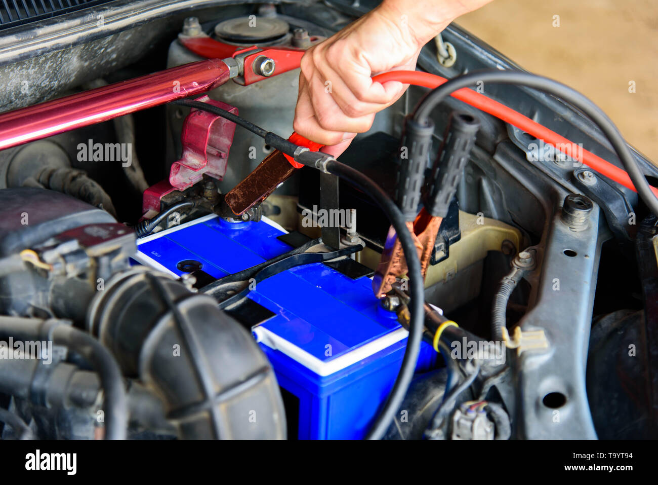 The man turn wrench for Change New Battery of old car - Stock Image