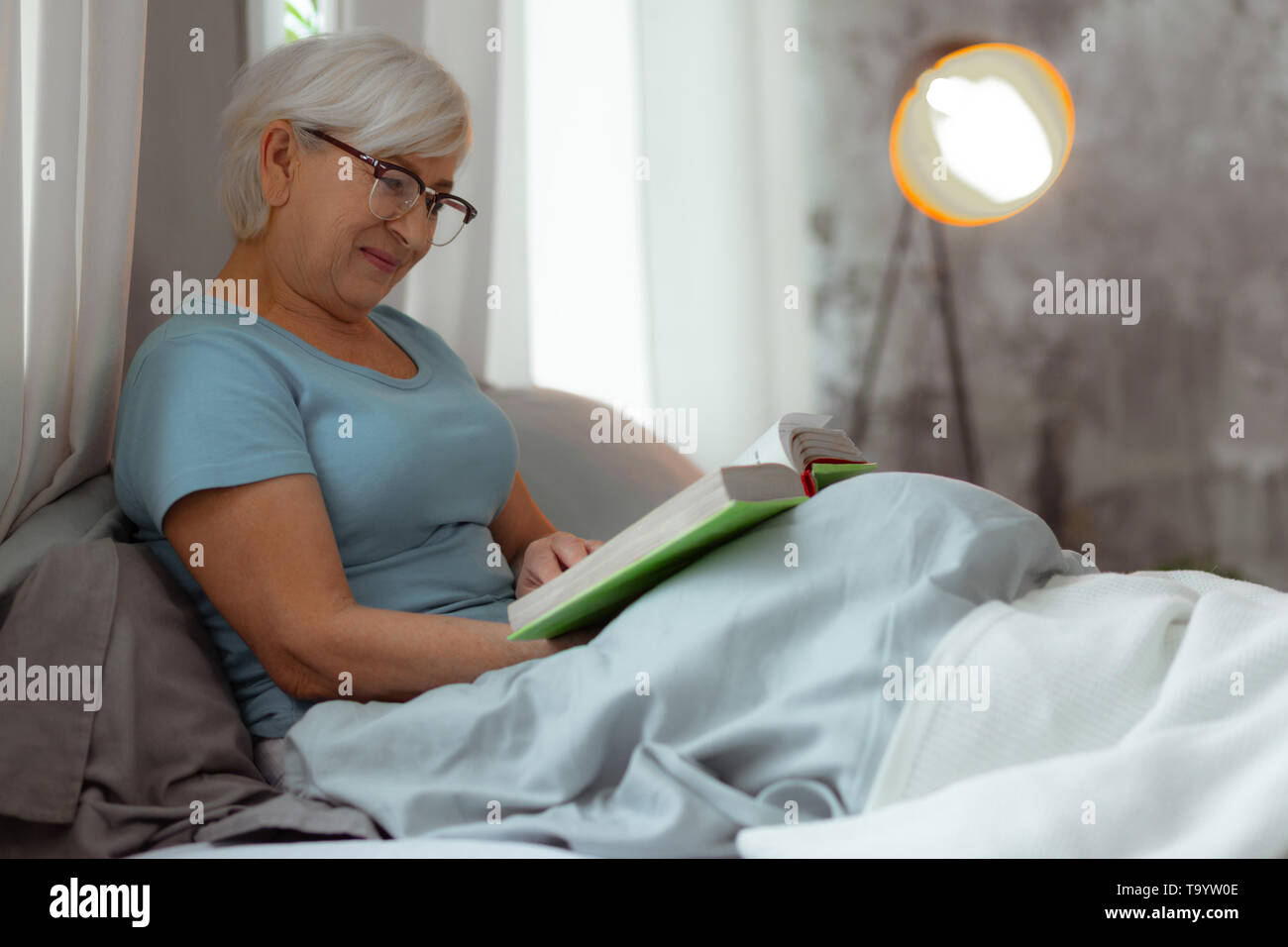 Charming lady lying in bed and engaging in book reading. - Stock Image
