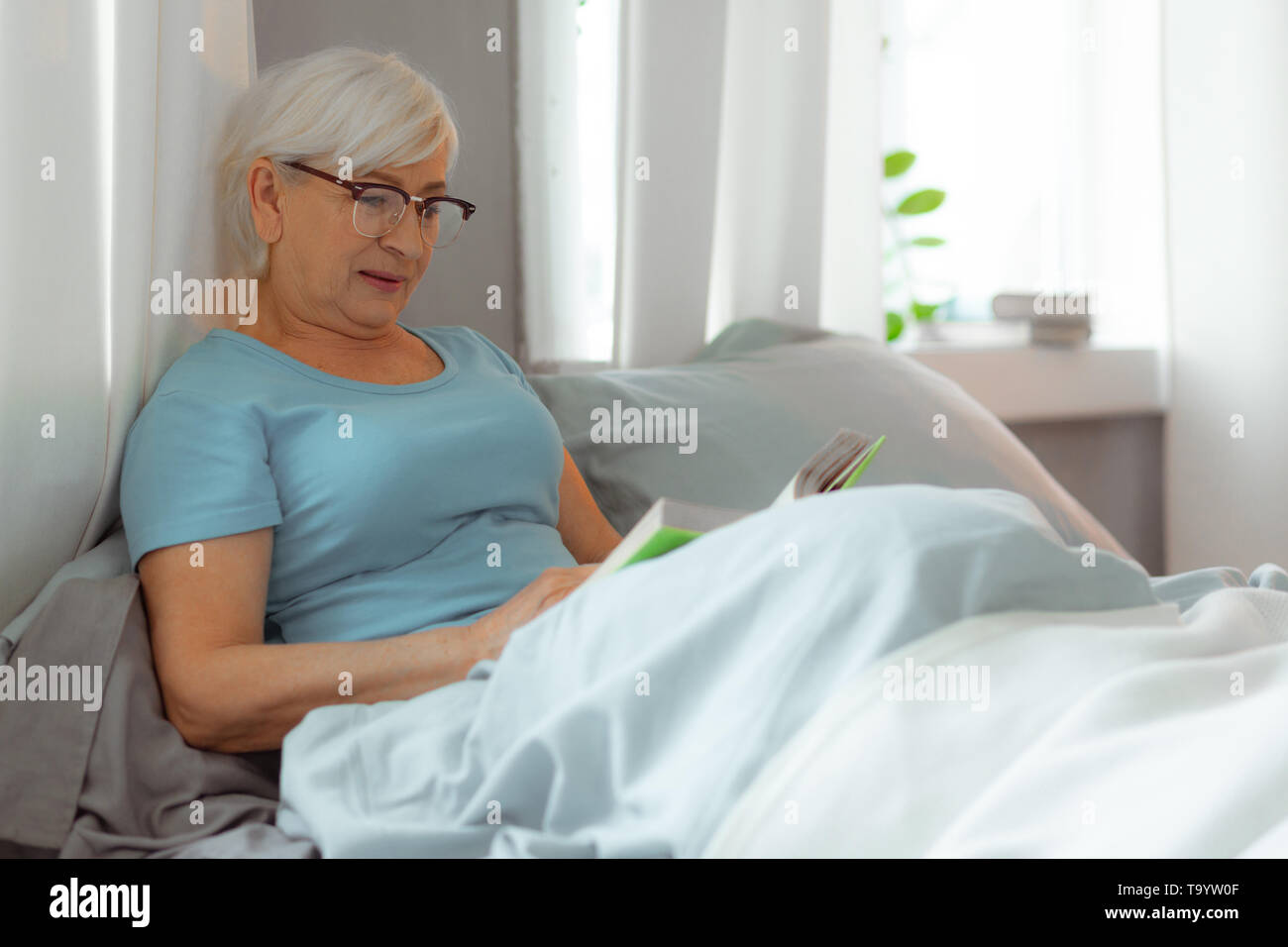 Charming lady lying in the bed and reading a book. - Stock Image