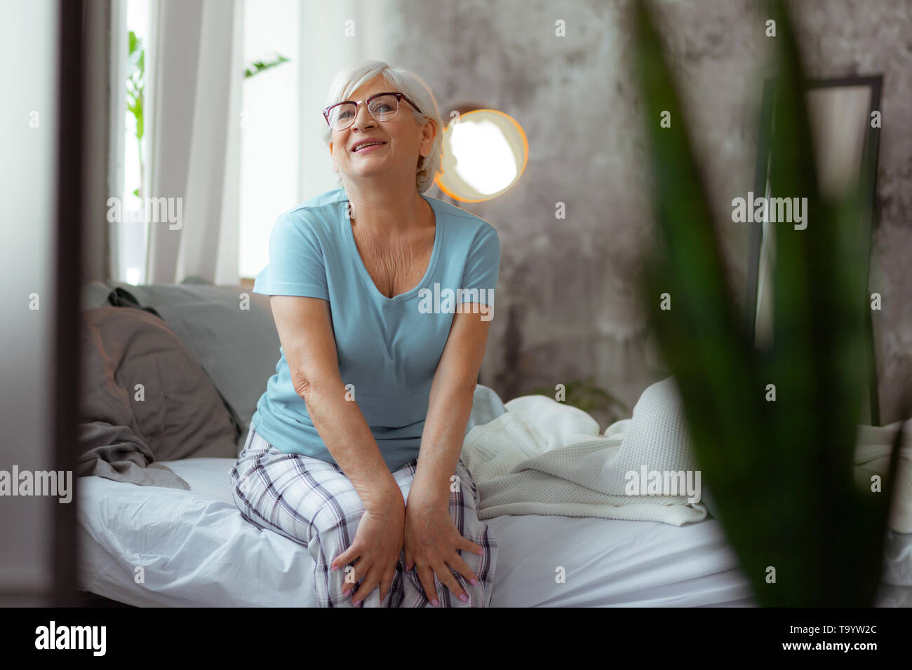 Smiling woman wearing eyeglasses and pajama sitting on the bed - Stock Image