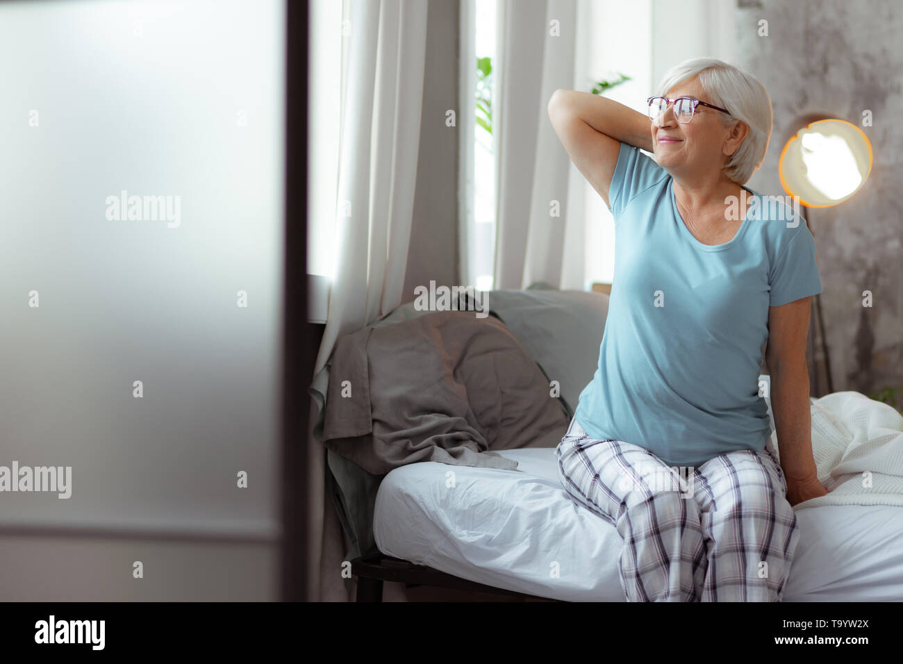 Nice-looking woman looking into the window while sitting on bed. - Stock Image
