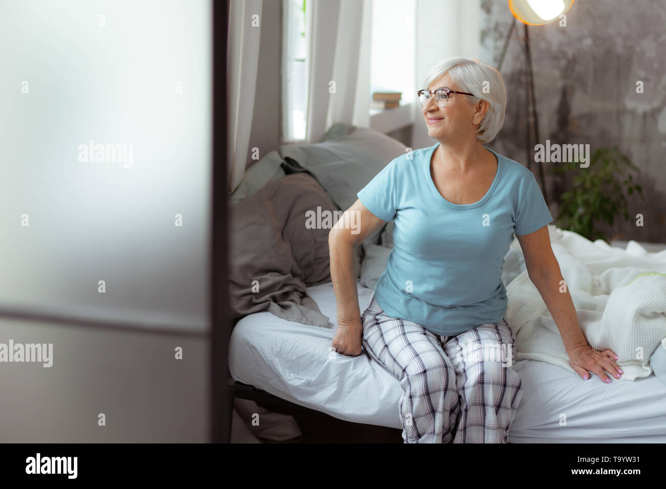 Good-looking woman looking into windows while sitting on the bed. - Stock Image