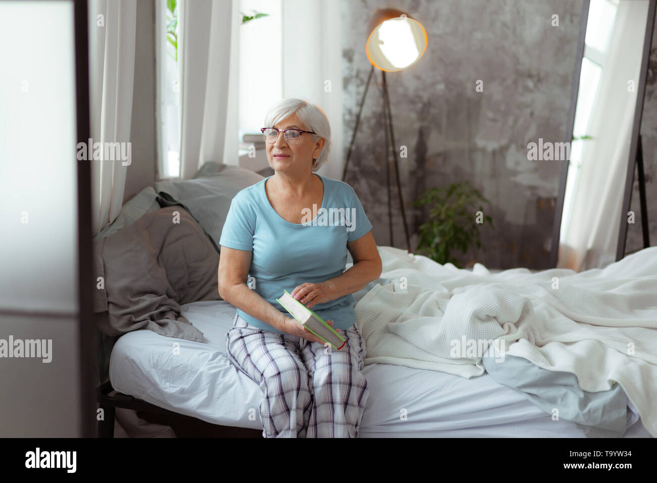 Beautiful woman preparing to open book while sitting on bed. - Stock Image