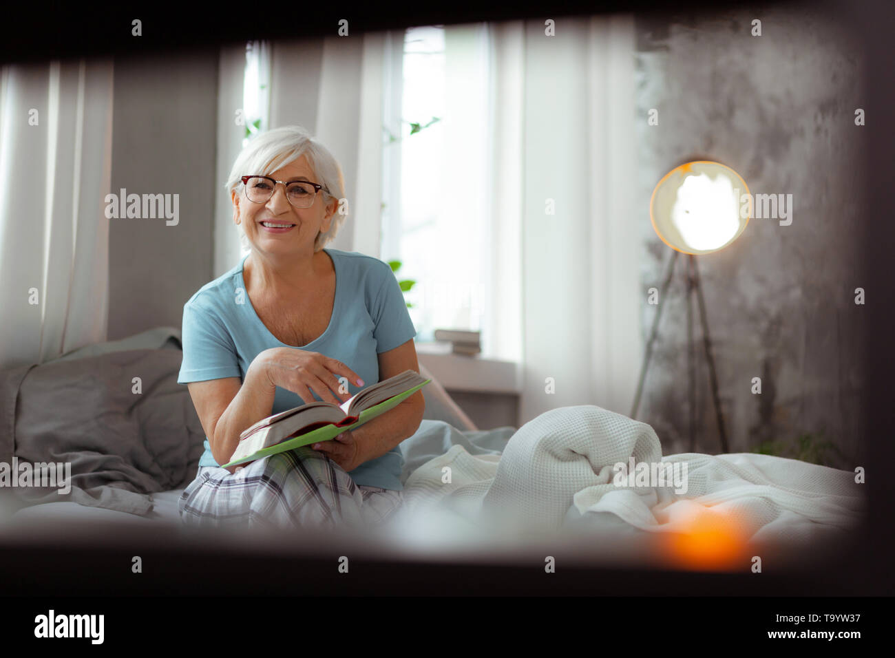 Beautiful lady sitting on the bed and opening the book. - Stock Image