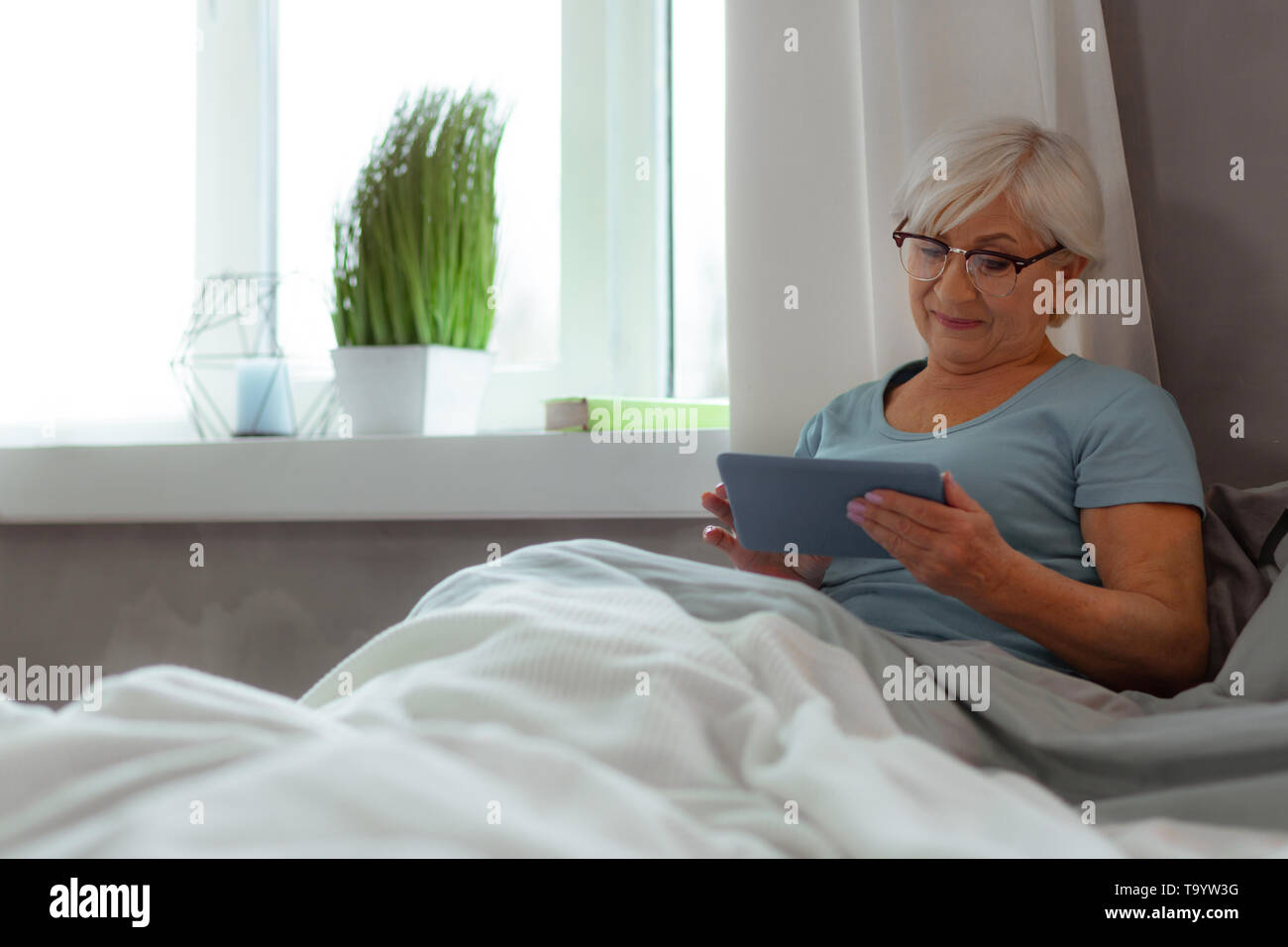 Glowing woman in blue t-shirt watching movie on a tablet - Stock Image