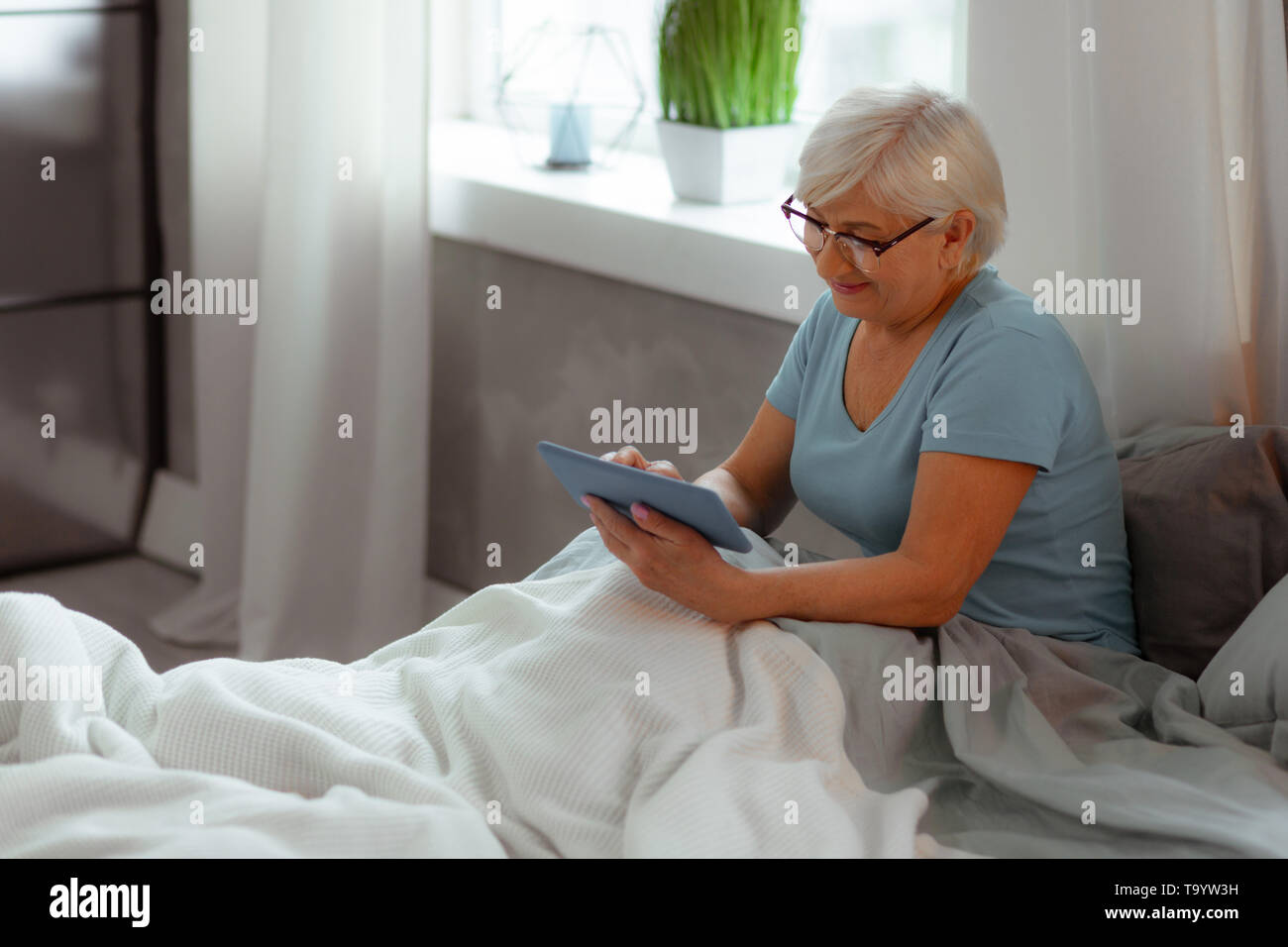 Nice-appealing lady watching a movie while lying in the bed - Stock Image