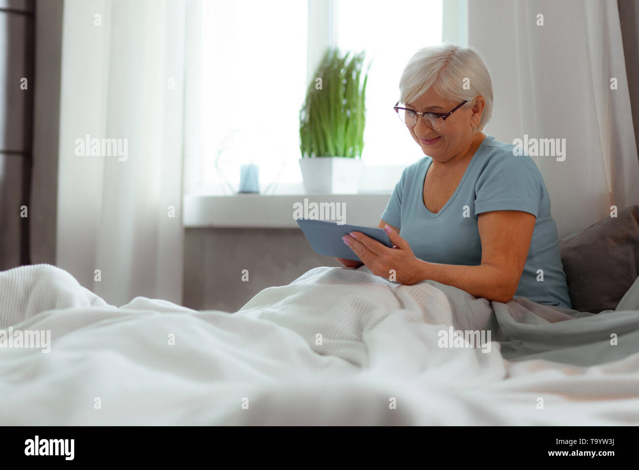 Smiling female clicking on the tablet while lying in bed - Stock Image