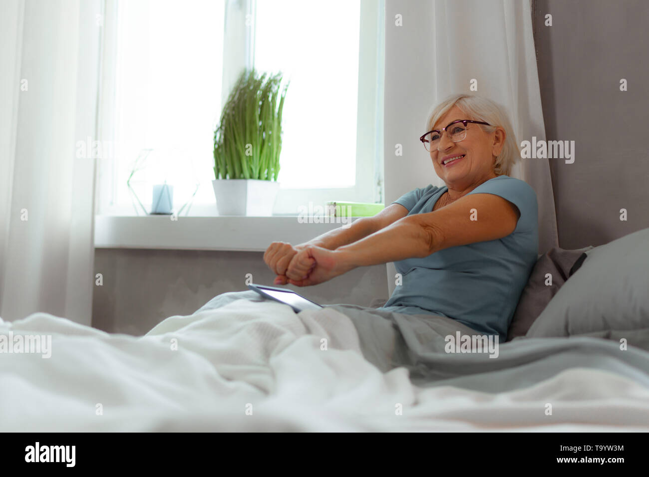 Active elderly female stretching her arms after sleeping - Stock Image