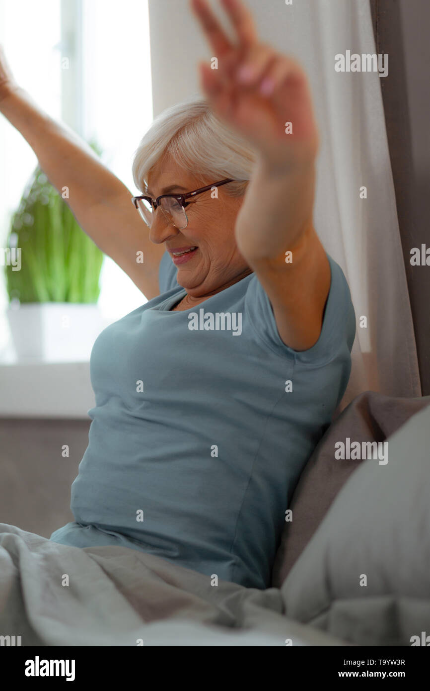 Attractive woman raising her hands while sitting in the bedroom. - Stock Image