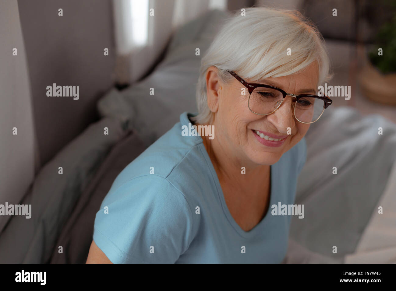 Face-portrait of wrinkled woman wearing eyeglasses and light-blue t-shirt - Stock Image