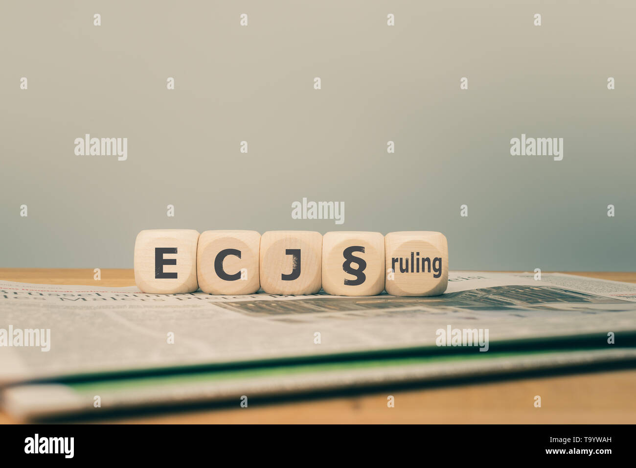 Symbol for a decision of the European Court of Justice (ECJ). 'ECJ ruling' written on cubes placed on a newspaper. - Stock Image