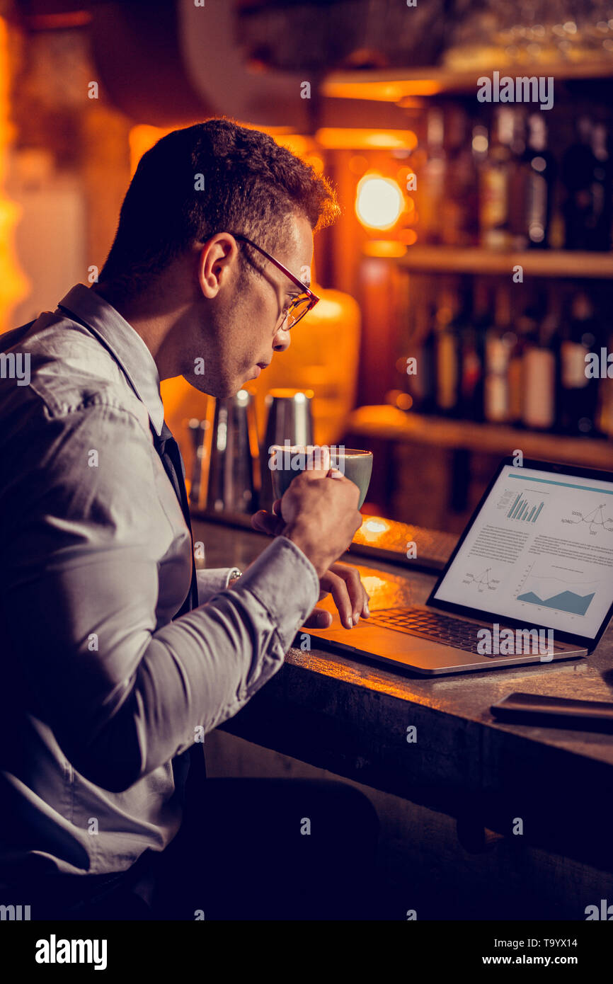 Freelancer drinking coffee and working sitting in his restaurant Stock Photo