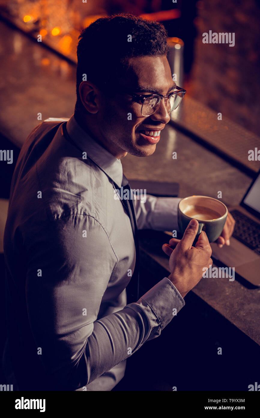 Handsome freelancer smiling having little coffee break - Stock Image