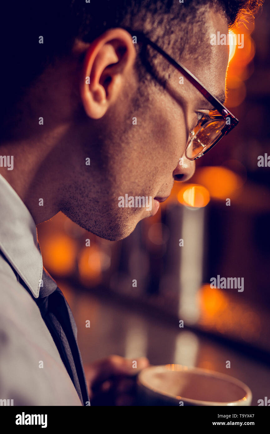 Close up of handsome dark-haired businessman wearing glasses - Stock Image