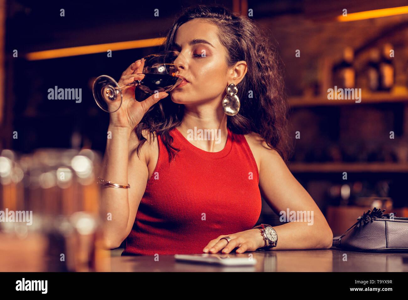 Beautiful woman wearing nice earrings drinking red wine - Stock Image