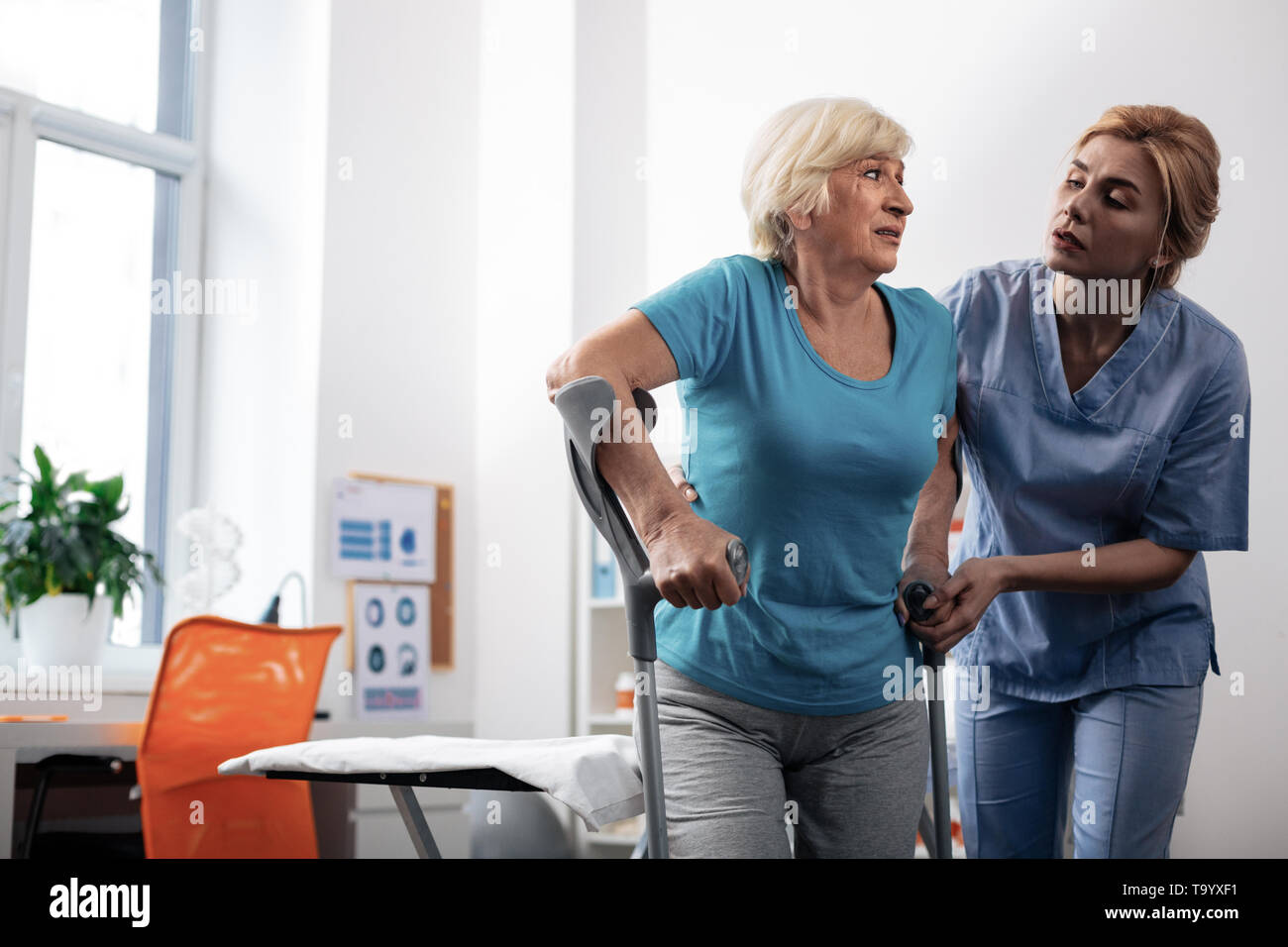 Nice pleasant nurse helping her patients to walk - Stock Image
