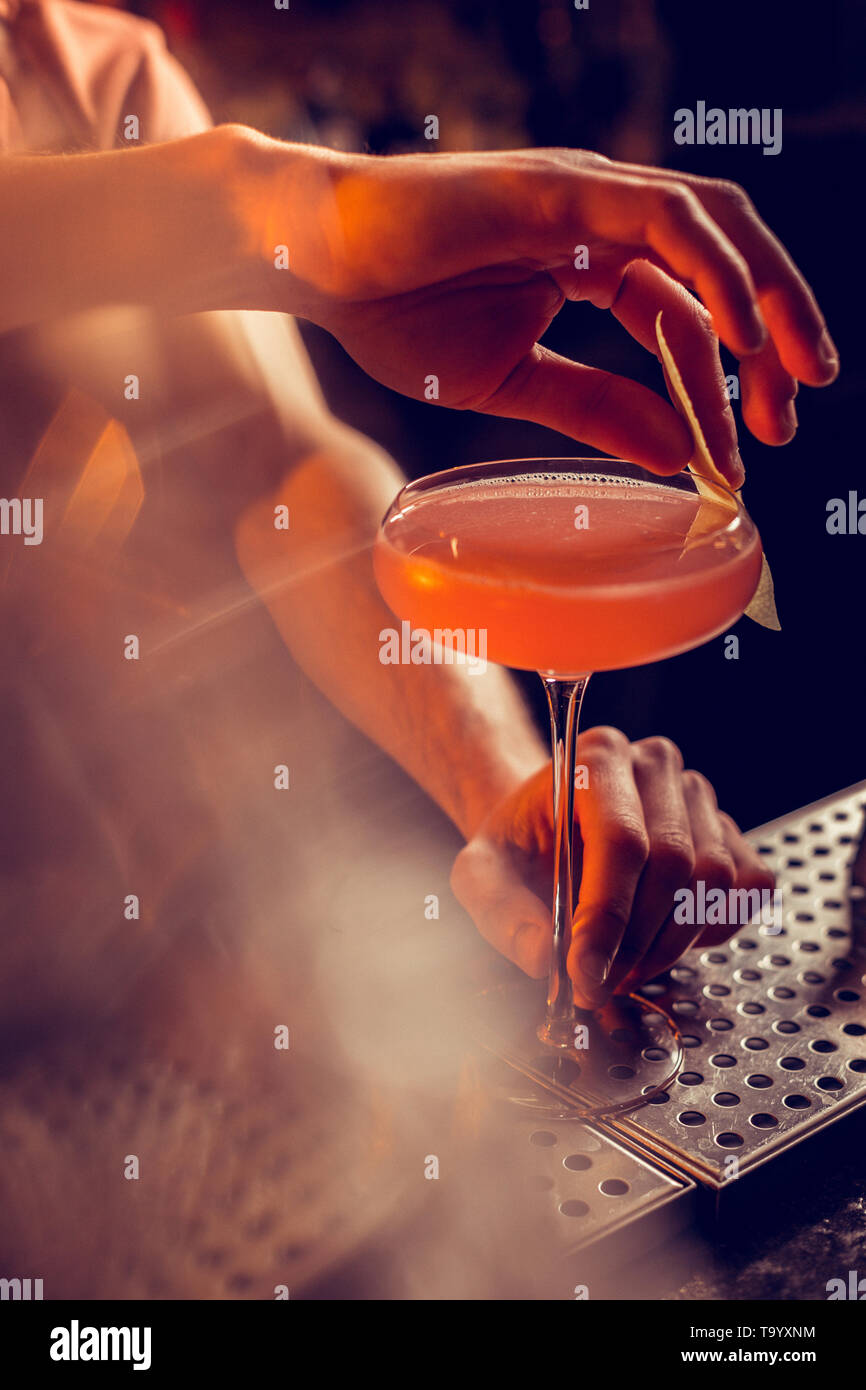 Top view of barman finishing nice alcohol fruit cocktail - Stock Image