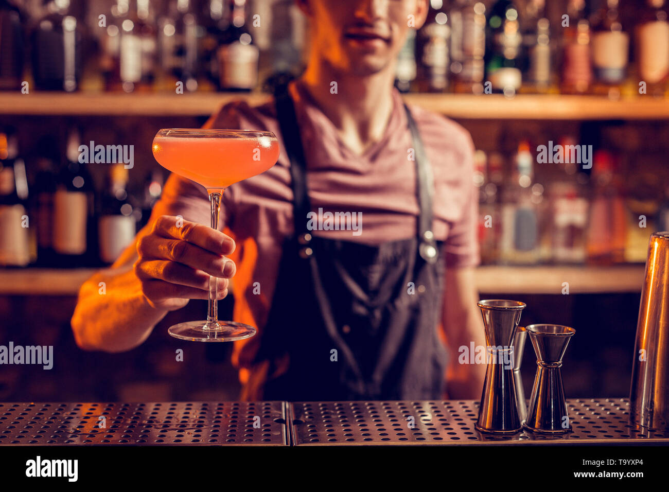 Barman wearing apron showing nice alcohol cocktail - Stock Image
