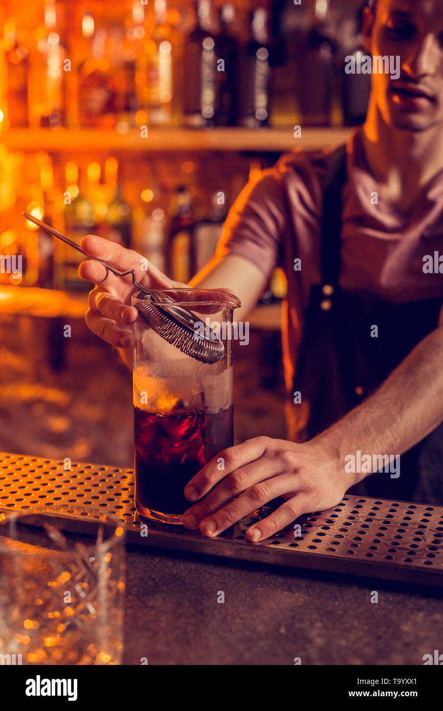Barman using modern equipment while making cocktail for client - Stock Image