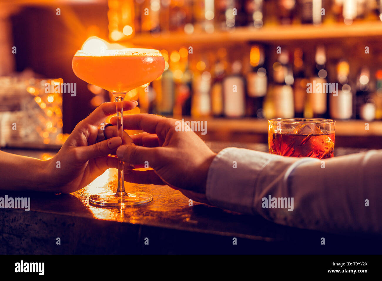 Close of man bringing nice cocktail for his girlfriend - Stock Image