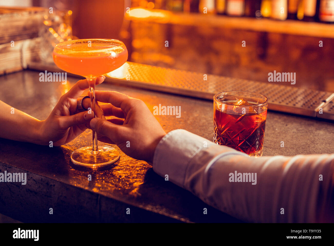 Caring boyfriend giving alcohol cocktail to his woman - Stock Image