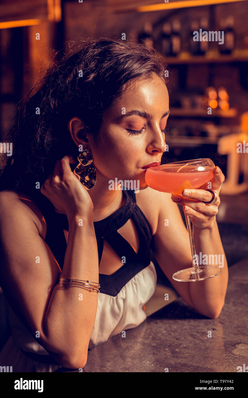 Beautiful woman with nice makeup drinking alcohol cocktail - Stock Image