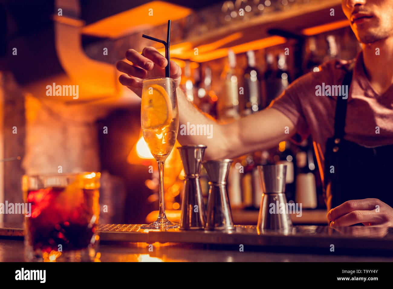 Barman putting straw into glass of cocktail with lemon - Stock Image