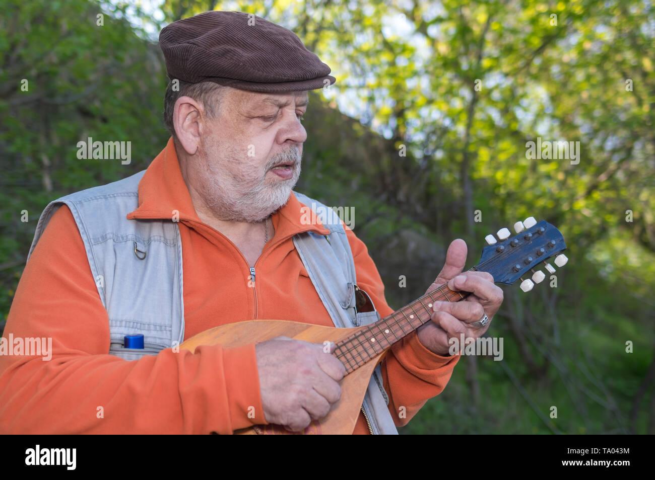 Outdoor portrait of senior man playing mandolin - Stock Image
