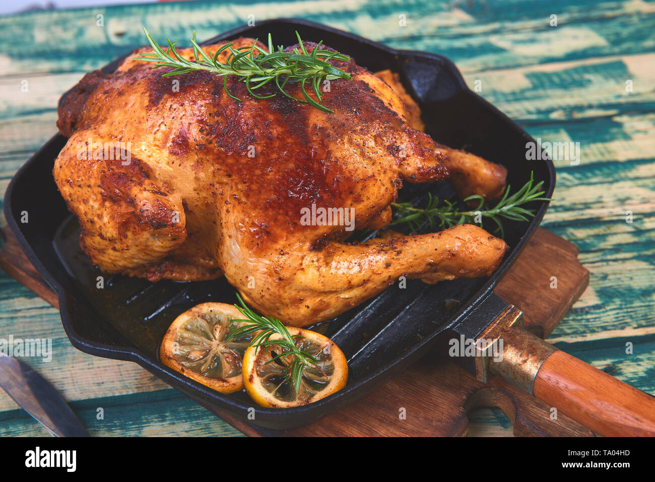 Baked whole chicken with apples in pan on wooden rustic background. Served on wooden board. Christmas chicken. - Stock Image