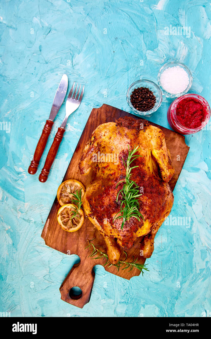 Baked whole chicken with sauces on wooden board on blue background. Christmas chicken. Dinner. Appetizer - Stock Image