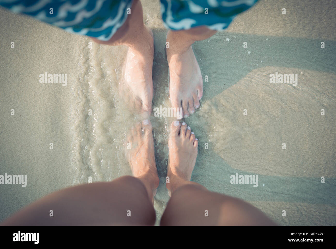 male and female feet on the sand. - Stock Image