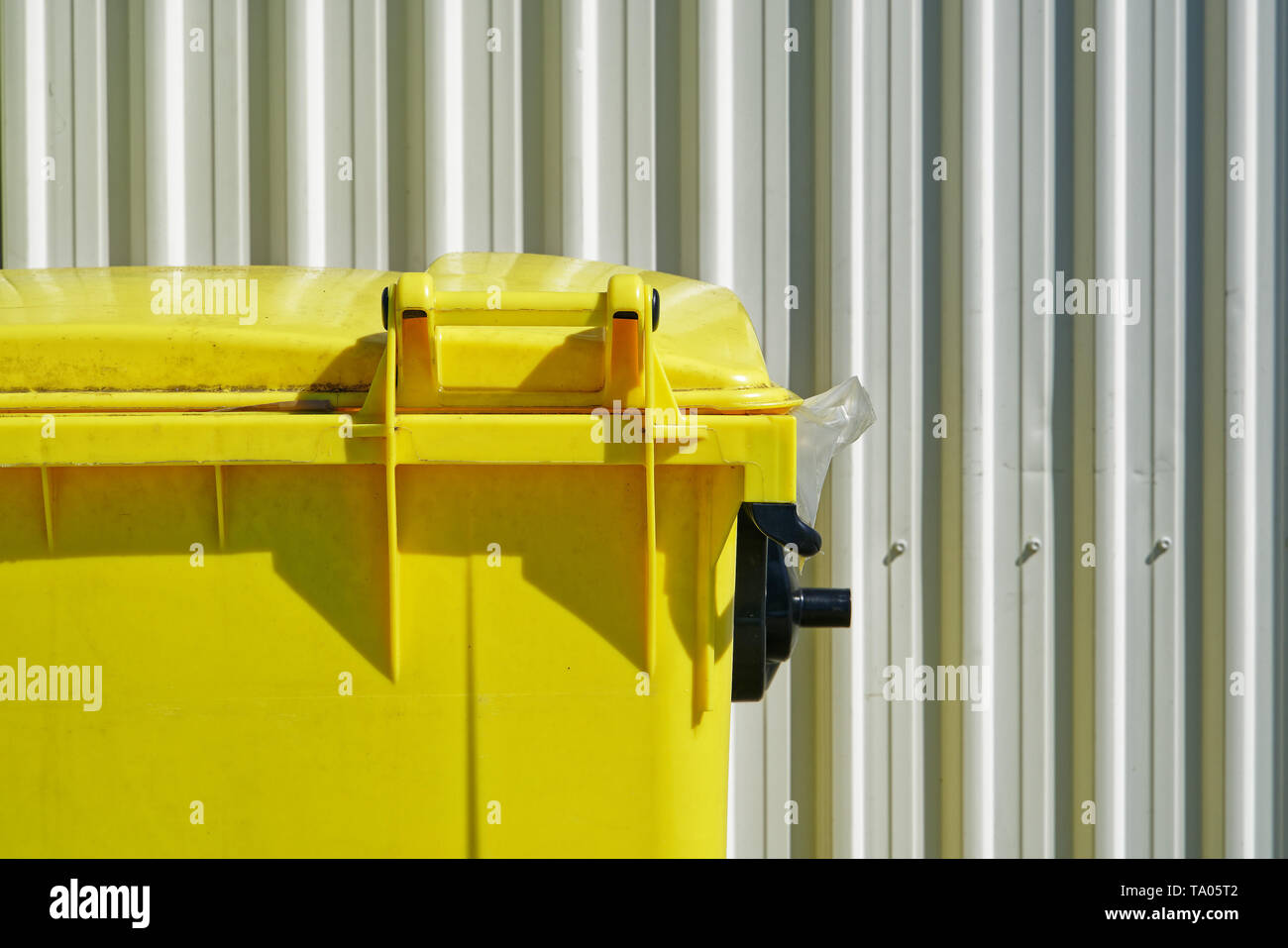 Bright yellow dumpster part view against a backdrop of a white industrial corrugated cladding or wall siding. - Stock Image