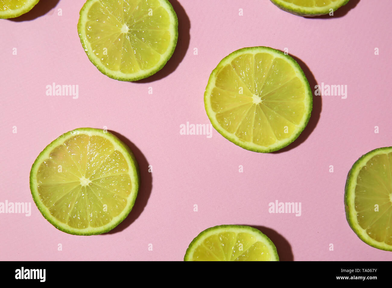 Many slices of lime on color background - Stock Image