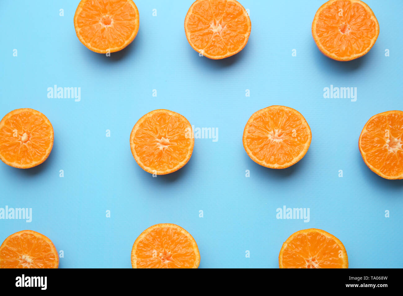 Many pieces of orange on color background - Stock Image