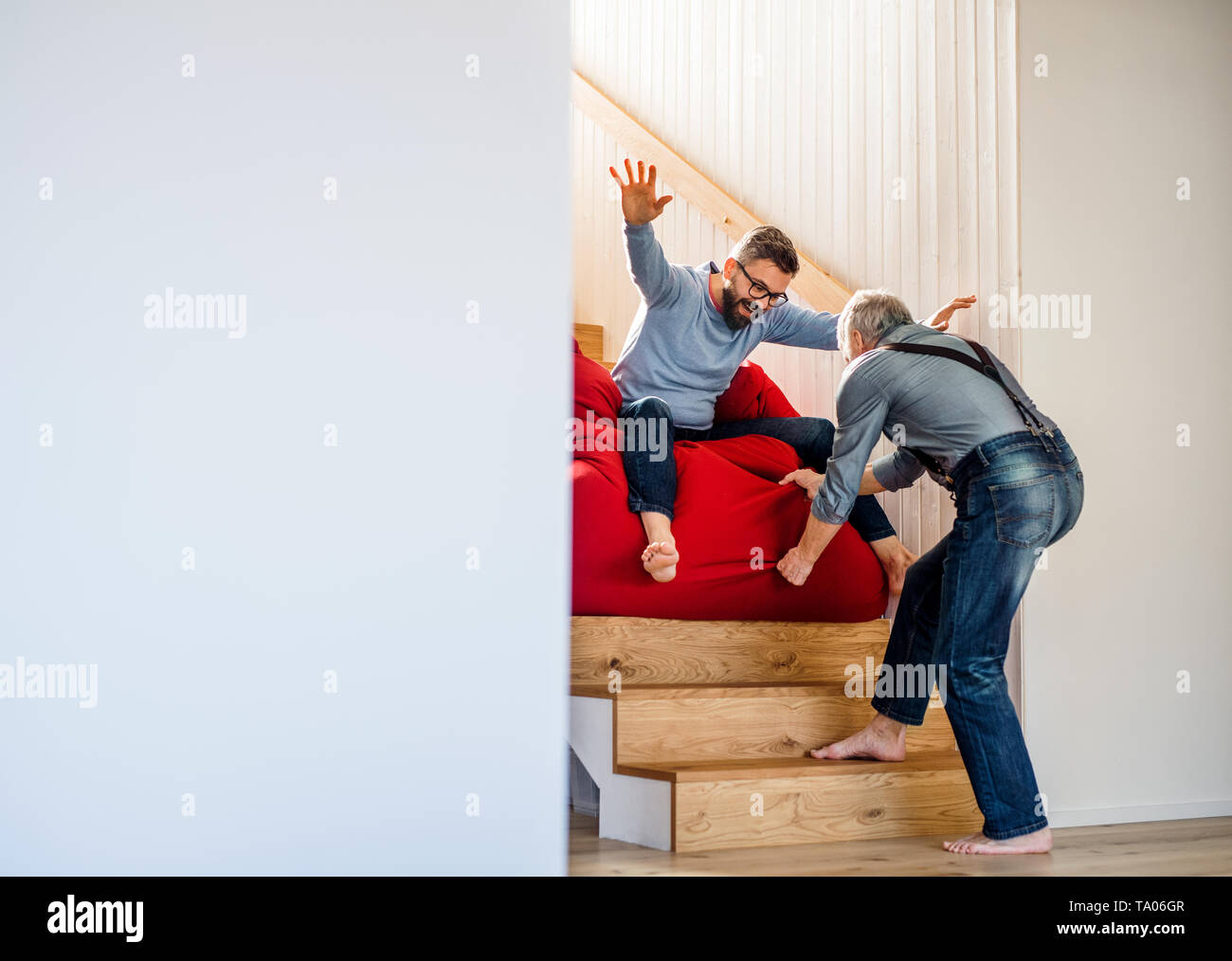 An adult hipster son and senior father sliding on stairs indoors at home, having fun. - Stock Image